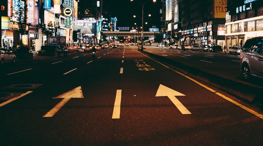 road at night with an arrow