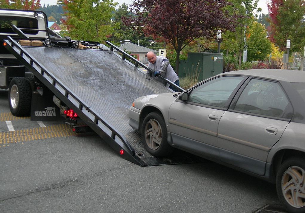 bald man towing a grey car for assistance