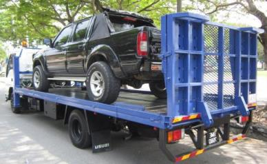 black pickup being towed for assitance