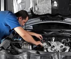 man in a blue shirt doing repair of a car engine