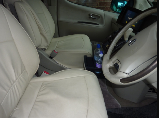 vanilla colored leather car seats with 2 bottled waters